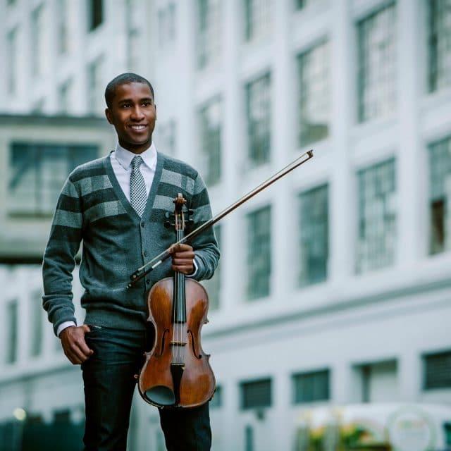 Man holding violin smiling