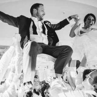 Happy couple does chair dance during the Hora