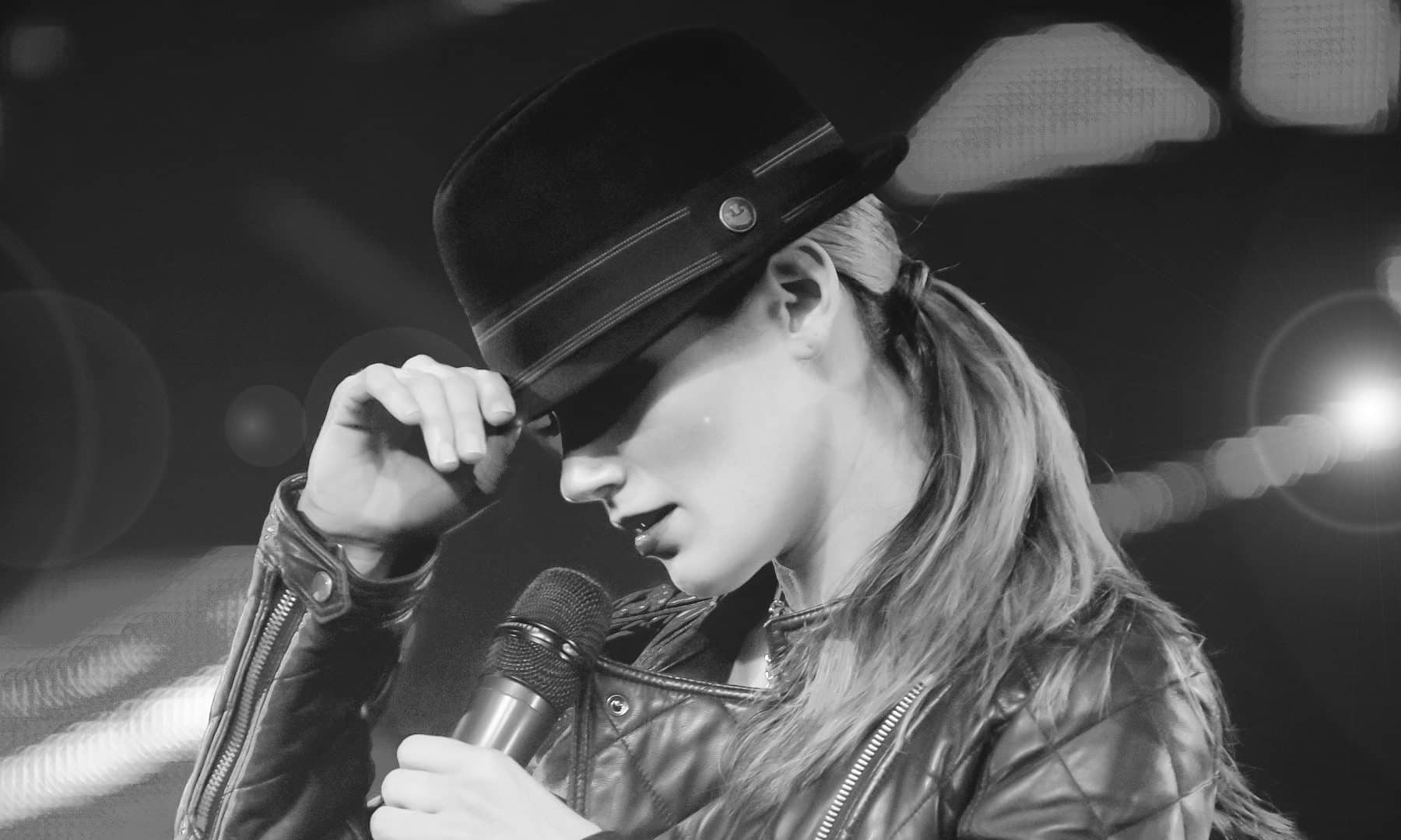 Singer of Soho band adjusts her hat while singing at Boston corporate event